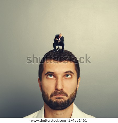 small angry boss screaming at big stupid man over grey background - stock photo