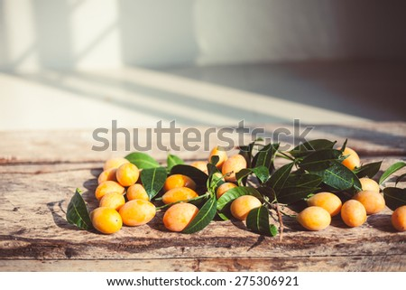 Small apricots on wooden background - summer photography background. 