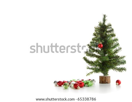 Small artificial tree with ornaments on white background - stock photo