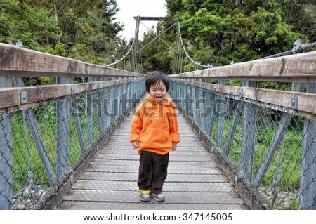 Small asian boy sticking out his tongue cheekily on a wooden bridge in rural area - stock photo