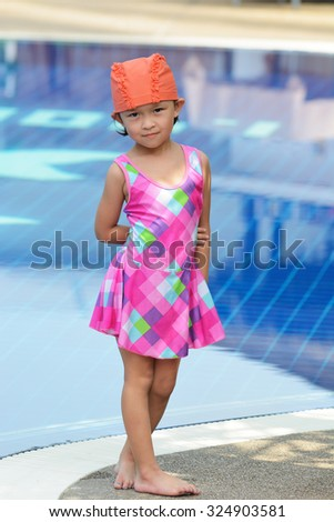 Small asian kid in swimming suit at the pool. - stock photo