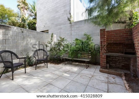 Small Australian apartment courtyard with paving and cane outdoor chairs - stock photo