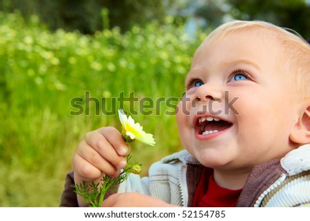 small baby boy holding a daisy in his hand and laughing in the field of flowers - stock photo