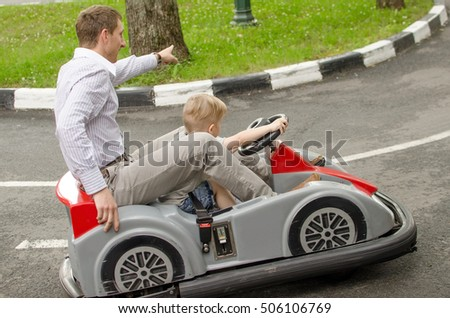 Small baby boy is enjoying driving small car in the park