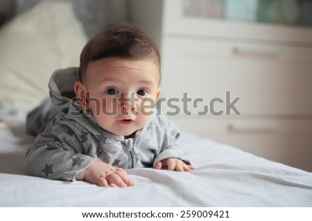 Small baby crawling on the bed in white room.On his face interest and wondering.European. - stock photo