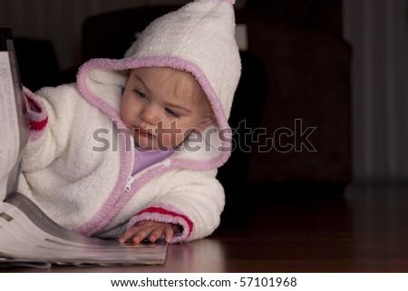 Small baby girl flipping through a magazine - stock photo