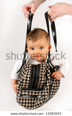 small baby girl in the hanging inside of the bag - stock photo