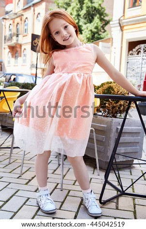 Small baby girl pretty kid happy childhood wear fashion dress sneakers walk run on the street cafe restaurant bright hair color cute smile building chair summer dance daughter - stock photo