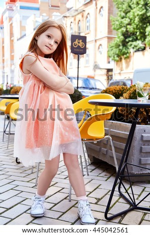 Small baby girl pretty kid happy childhood wear fashion dress sneakers walk run on the street cafe restaurant bright hair color cute smile building chair summer dance daughter