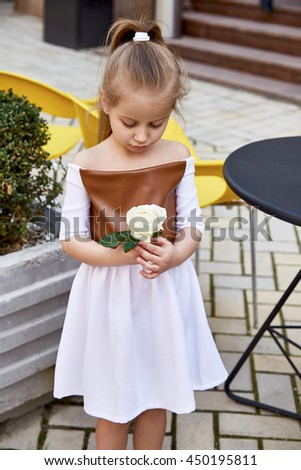 Small baby girl pretty kid happy childhood wear fashion dress walk run on the street cafe restaurant blonde hair color cute smile building chair summer dance daughter flower rose  - stock photo