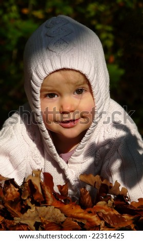 Small baby in autumn forest with yellow maple leaves - stock photo