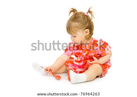 Small baby in red dress with toy cup and spoon isolated