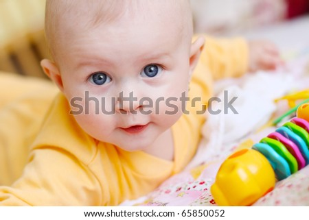 Small baby on the bed with the rattle bag watching you and smiling dressed in the orange night suit - stock photo