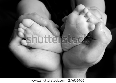 small baby's feet in daddy's hands on black - stock photo