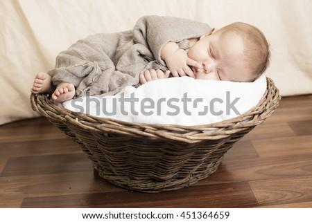 Small Baby sleeping inside wooden basket - stock photo