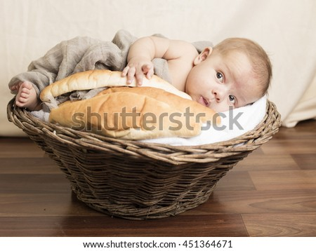Small Baby sleeping inside wooden basket with bread in hand - stock photo