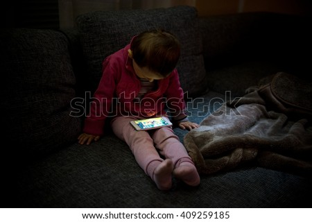 Small baby using Smartphone in the dark living room