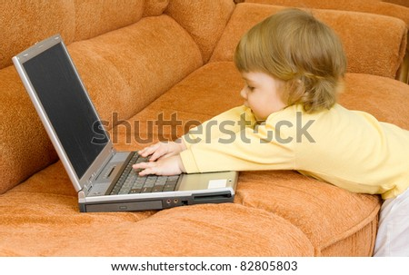 Small baby with grey laptop at home