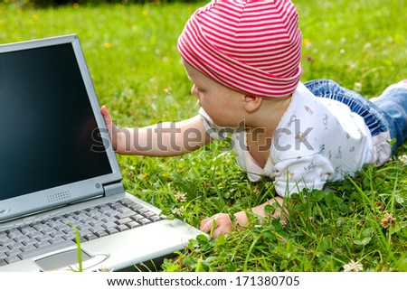 Small baby with laptop on the meadow - stock photo