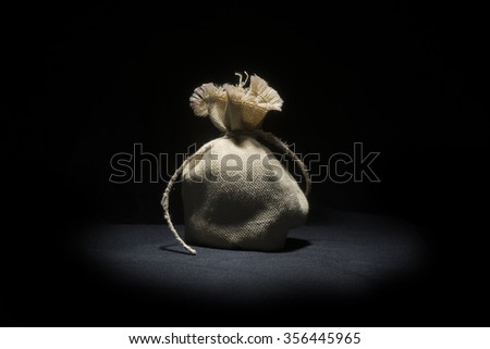 small bag jute on black background  - stock photo