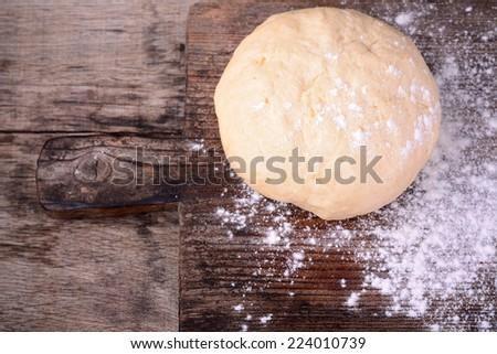 Small balls of fresh homemade dough on floured wooden board  Selective Focus, Focus one third into the first dough - stock photo