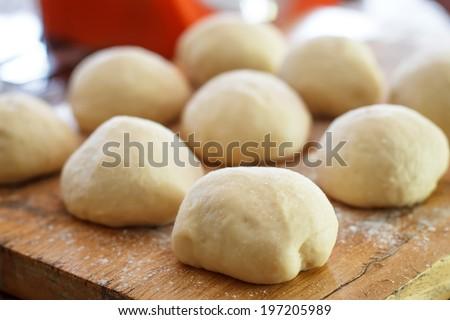 Small balls of fresh homemade pizza dough on floured wooden board - stock photo