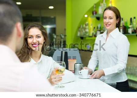 Small bar with female barista and two clients at counter. Focus on girl