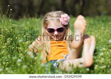 small barefooted girl in grass - stock photo
