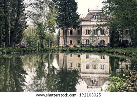 Small baroque castle reflecting in a lake - stock photo