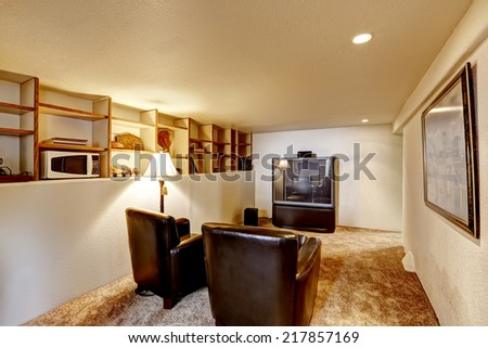 Small basement room interior. Two leather chairs and tv.