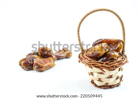 Small basket with dates on white background - stock photo