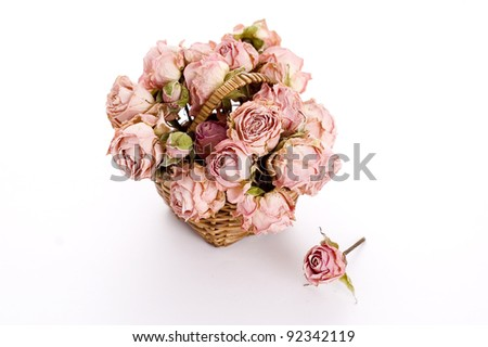 small basket with dried pink roses isolated on white background
