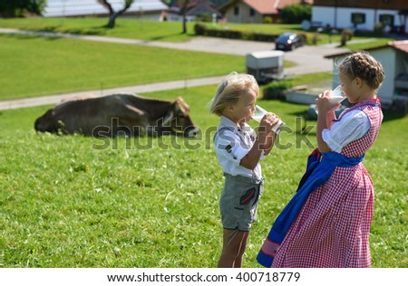 Small Bavarian children drink milk on the meadow with cow - stock photo