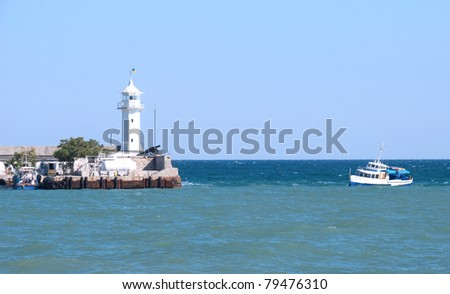 Small beacon in a sea gulf and a boat in the sea