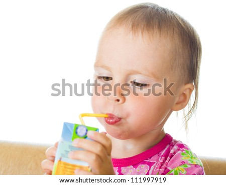 Small beautiful baby drinking juice from straw on a white background.