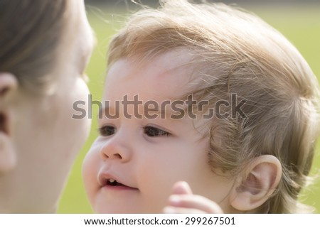 Small beautiful blond baby boy with curly hair smiling to his young mother holding him on hands outdoor sunny day on green grass natural background, horizontal picture - stock photo