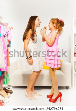 Small beautiful girl applies make-up on her friend - stock photo