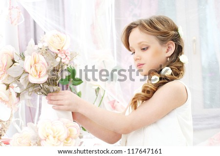 small beautiful girl in white dress holding flowers