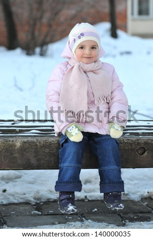small beautiful girl playing in park.  winter day