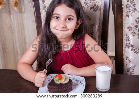 Small beautiful middle eastern girl with chocolate cake with pineapple, strawberry, milk, red dress, dark eyes, long hair, drinking, eating at home, sitting, smiling. looking at camera. studio shot.  - stock photo