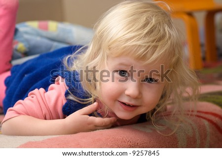 Small beautiful smiling girl with blonde hair at home background