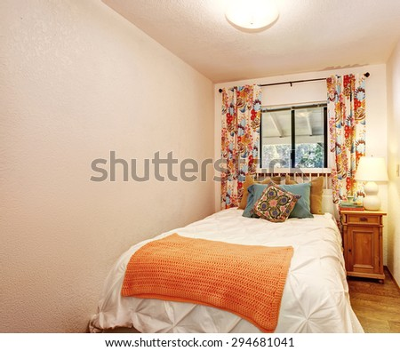 Small bedroom with white and orange bedding, along with hardwood floor.