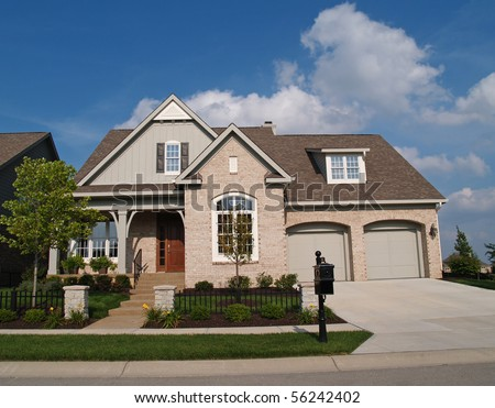 Small beige brick home with a two car garage in the front. - stock photo