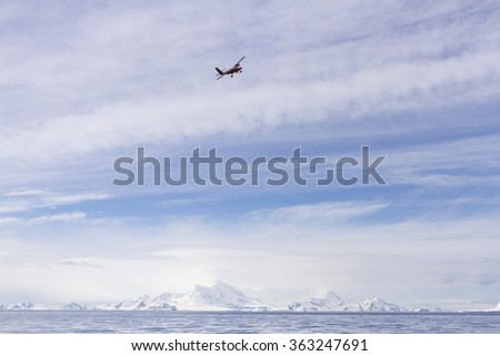 Small biplane flying over Deception Island, Antarctica.