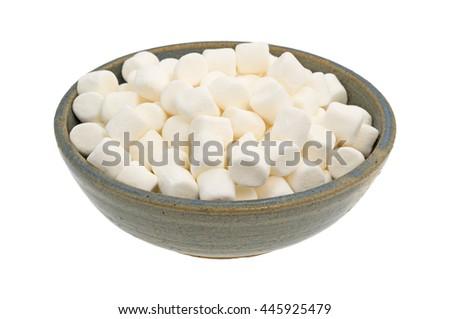 Small bite size marshmallows filling an old stoneware bowl. - stock photo