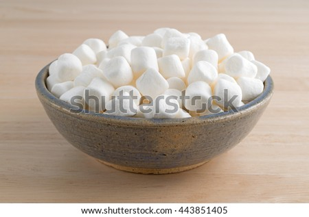 Small bite size marshmallows filling an old stoneware bowl on a wood table.