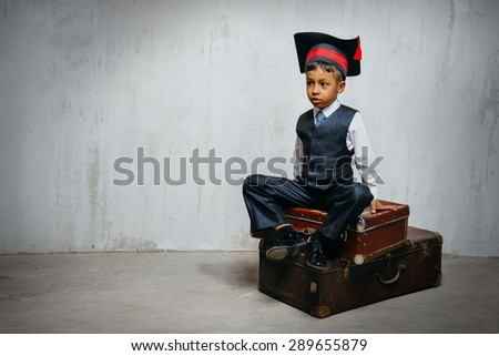 small black boy in suit and graduation hat sits on the old suitcases and look left. copy space left, instagram toned - stock photo