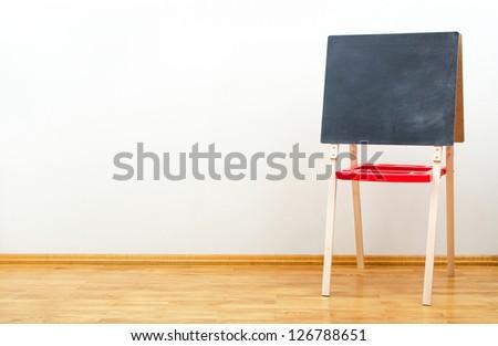 Small blackboard near the wall in empty room - stock photo