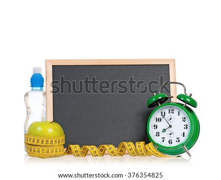 Small blackboard with clock, water and apple, isolated on white background - stock photo