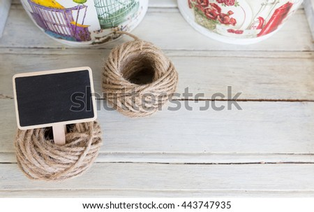 Small blackboard with hemp rope on vintage white cabinet - stock photo